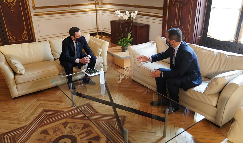 Moreno escucha al portavoz parlamentario del PP-A, José Antonio Nieto.