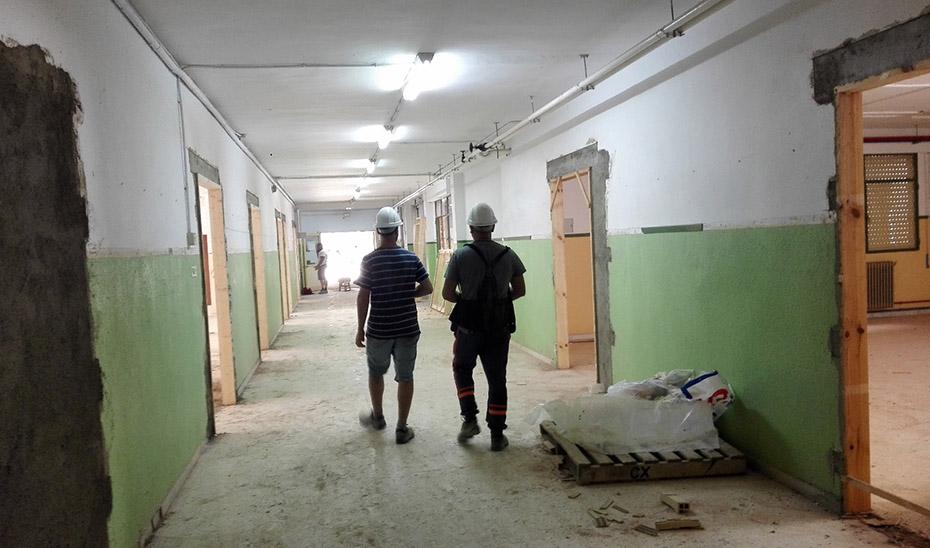 Dos trabajadores caminan por los pasillos de un centro escolar en construcción.