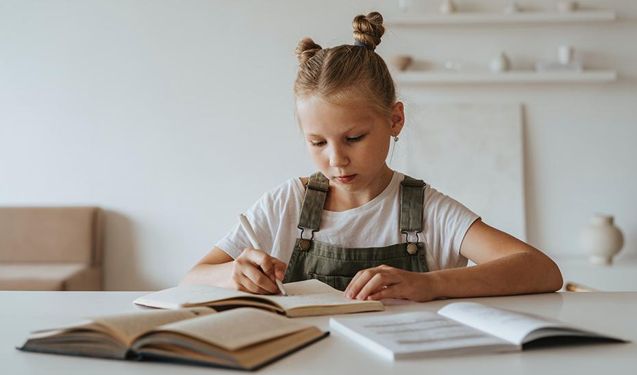 Una escolar realiza sus tareas con sus libros de texto.