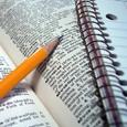 Imagen en la que se observa un primer plano de un bloc de notas con un lápiz amarillo encima.