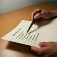 Imagen en la que se observan las manos de una persona, sujetando un bolígrafo y un folio.