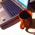 Imagen en la que se observa un ordenador portátil, junto a una taza de café.