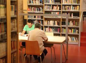 Personas leyendo en la biblioteca del centro