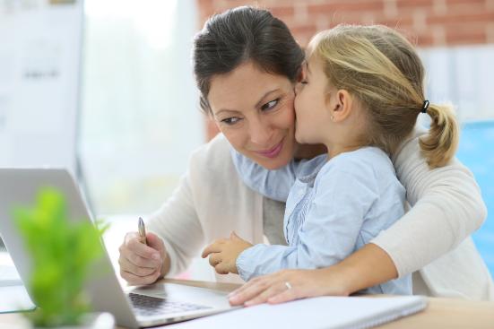 Fotografía de una madre ayudando a su hija con la tarea desde el portátil