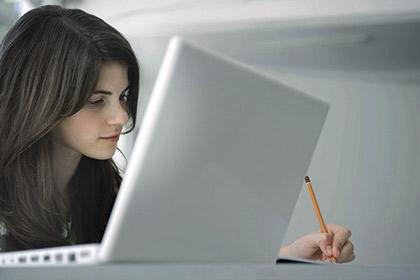 Mujer joven estudiante universitaria consultando un ordenador