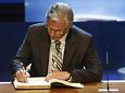 El juez Baltasar Garzón firma en el Libro de Honor de la Junta ante la mirada de Manuel Chaves, Francisco Girón, Manolo Escobar y Federico Mayor Zaragoza.