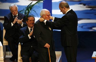 El sacerdote Francisco Girón recibe la Medalla de Andalucía de manos del presidente de la Junta, Manuel Chaves, con el aplauso de Federico Mayor Zaragoza y Tico Medina.