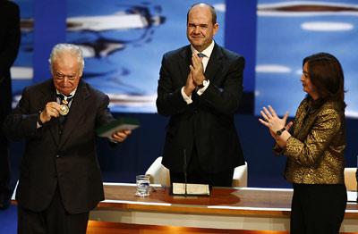 El periodista Tico Medina muestra su Medalla de Andalucía al público asistente en el Teatro de la Maestranza, con el aplauso de María del Mar Moreno y Manuel Chaves.