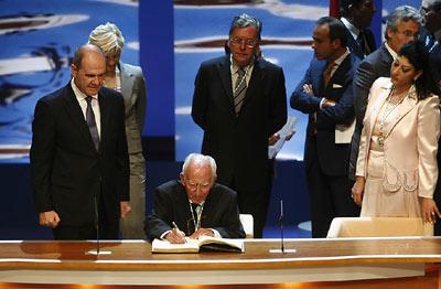 El sacerdote Francisco Girón firma en el Libro de Honor de la Junta de Andalucía, ante la mirada del presidente de la Junta.