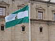 La bandera blanca y verde ondea al viento frente a la puerta principal          del Parlamento de Andalucía, durante el acto de homenaje a la insignia.