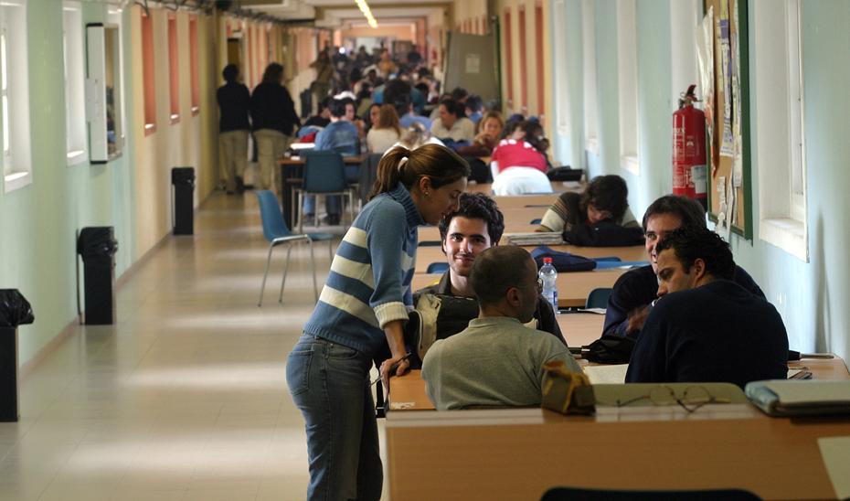 Universitarios andaluces en el pasillo de una facultad con mesas habilitadas para trabajos en grupo.