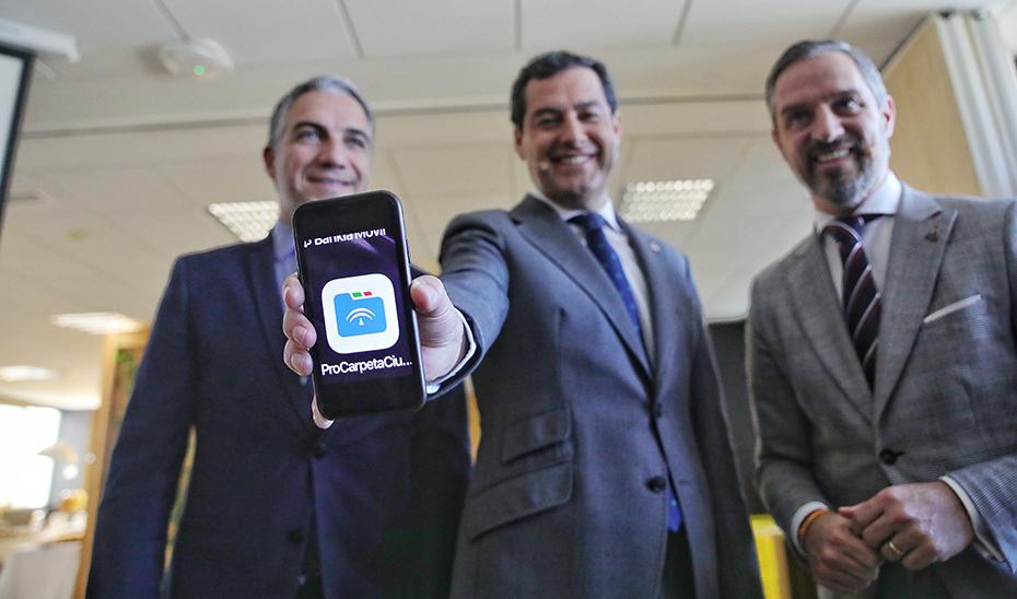 El presidente Juanma Moreno, flanqueado por Elías Bendodo y Juan Bravo, con la app Carpeta Ciudadana en su móvil.