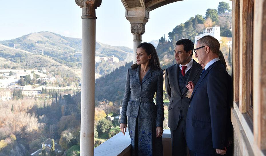 La Reina Letizia y el presidente andaluz atienden a las explicaciones de una responsable de la muestra desde una de las balconadas del Palacio de Carlos V.
