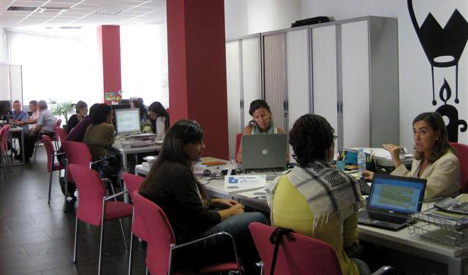 Personal y usuarios en una unidad de orientación laboral en horario de oficina.