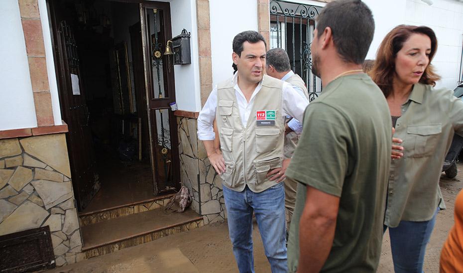 Juanma Moreno y la alcaldesa de Alhaurín el Grande en la puerta del domicilio de uno de los vecinos afectados por las trombas.