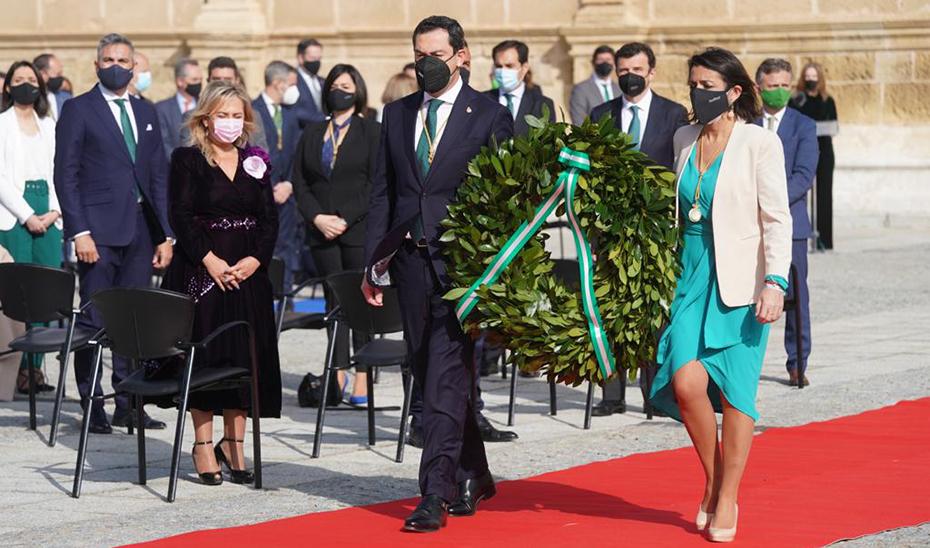 El presidente de la Junta de Andalucía y la del Parlamento, Juanma Moreno y Marta Bosquet, trasladan una corona de laurel en homenaje a las víctimas de la pandemia de Covid-19.