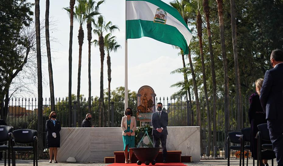 El presidente de la Junta, Juanma Moreno, junto a la del Parlamento, Marta Bosquet, en el izado de la Bandera.