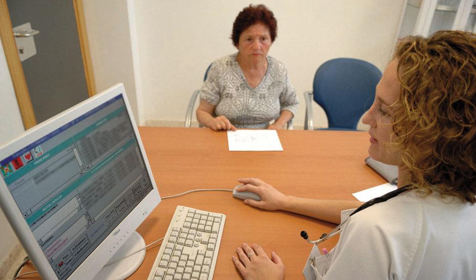 Una médico consulta el historial médico de una paciente en la plataforma Diraya.