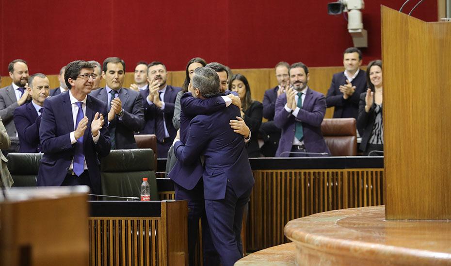 El presidente Juanma Moreno felicita al consejero de Hacienda, Juan Bravo, tras la aprobación de los Presupuestos para 2020.