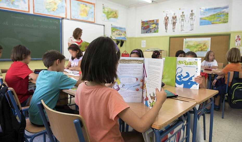 Alumnos de Primaria leen sus libros de texto en clase.