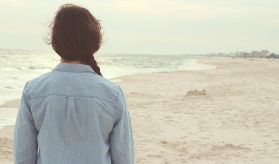 Una mujer joven camina por la playa.