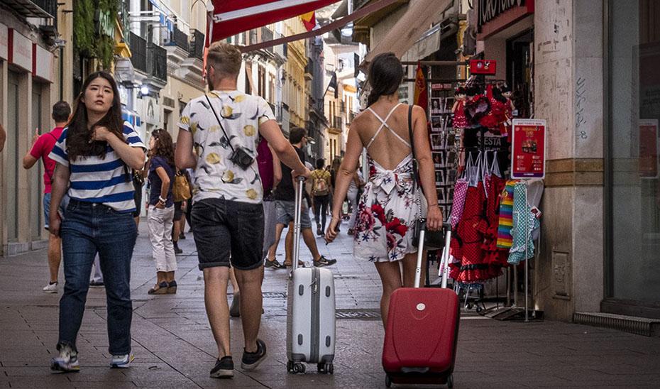 Turistas arrastran sus maletas por una calle del centro histórico de Sevilla.