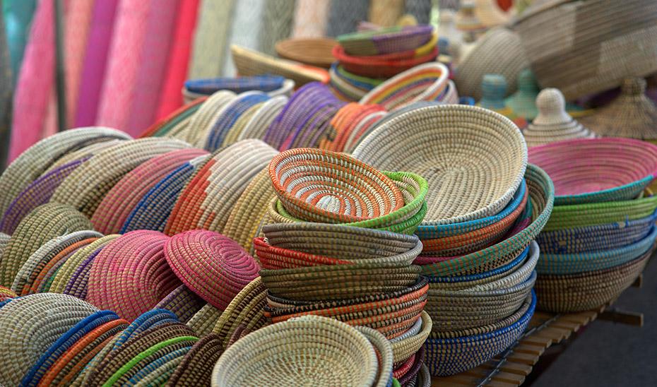 Cestas de colores fabricadas artesanalmente en el exterior de un comercio artesano.