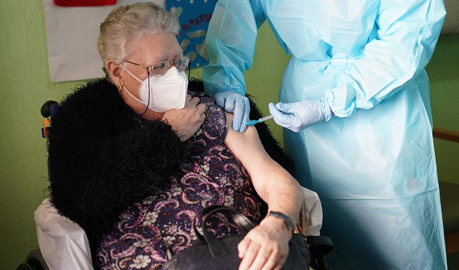 Una enfermera administra la primera dosis de la vacuna a una anciana.