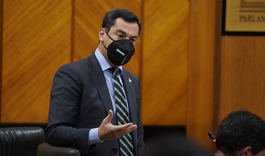 Juanma Moreno dirigiéndose a uno de los portavoces de los grupos parlamentarios.
