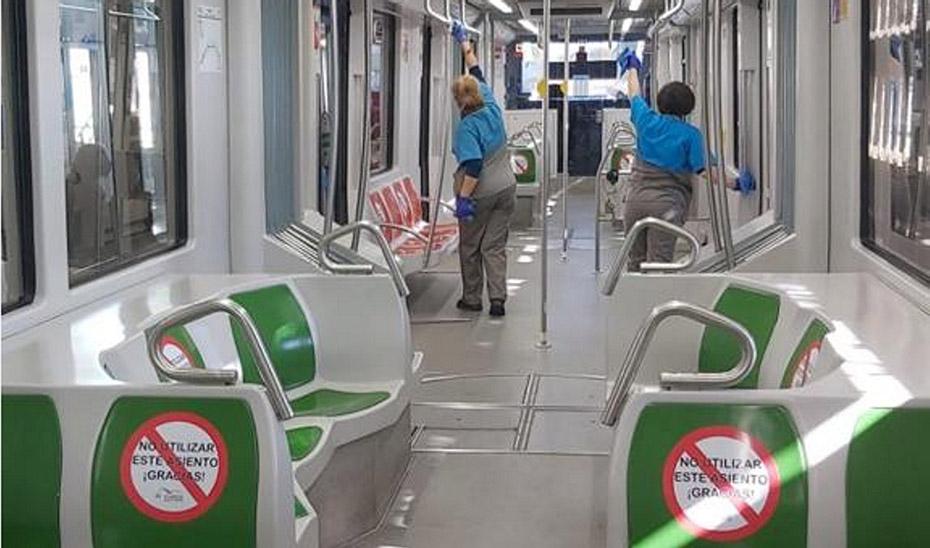 Dos mujeres limpian el interior de los vagones del metro de Sevilla.