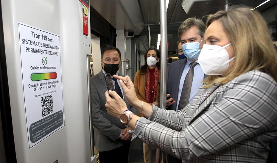 La consejera lee con su móvil el código QR en uno de los vagones del metro de Sevilla.