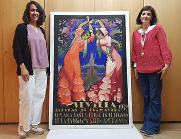 Las conservadoras del Museo de Artes y Costumbres Populares de Sevilla María Venegas (izquierda) y Elena Hernández (derecha), junto a uno los carteles almacenados en el recinto expositivo.