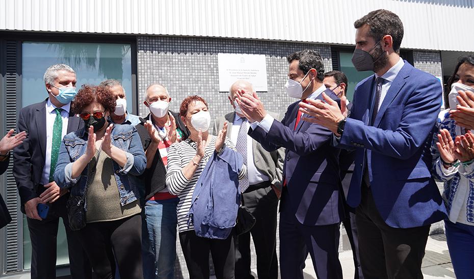 El presidente andaluz aplaude junto a autoridades y vecinos tras la inauguración del centro.