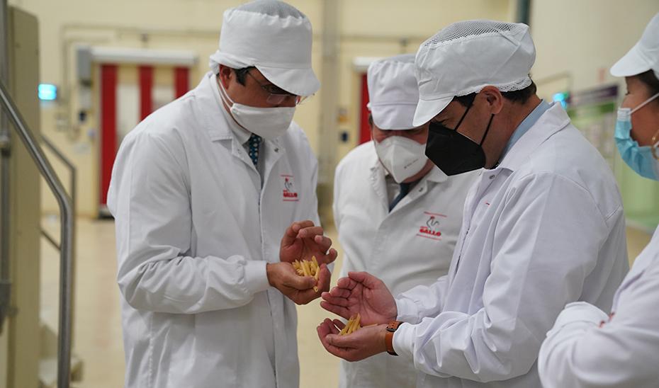 Juanma Moreno supervisa uno de los productos de Pastas Gallo durante su visita la fábrica.