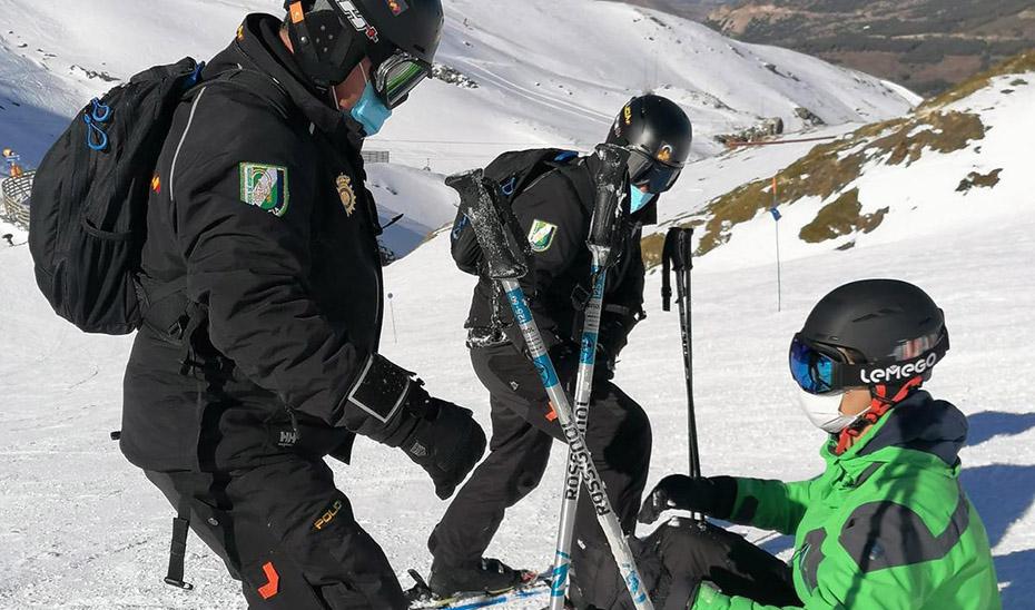 Dos agentes de la Unidad de Policía Adscrita atienden a una persona en Sierra Nevada.