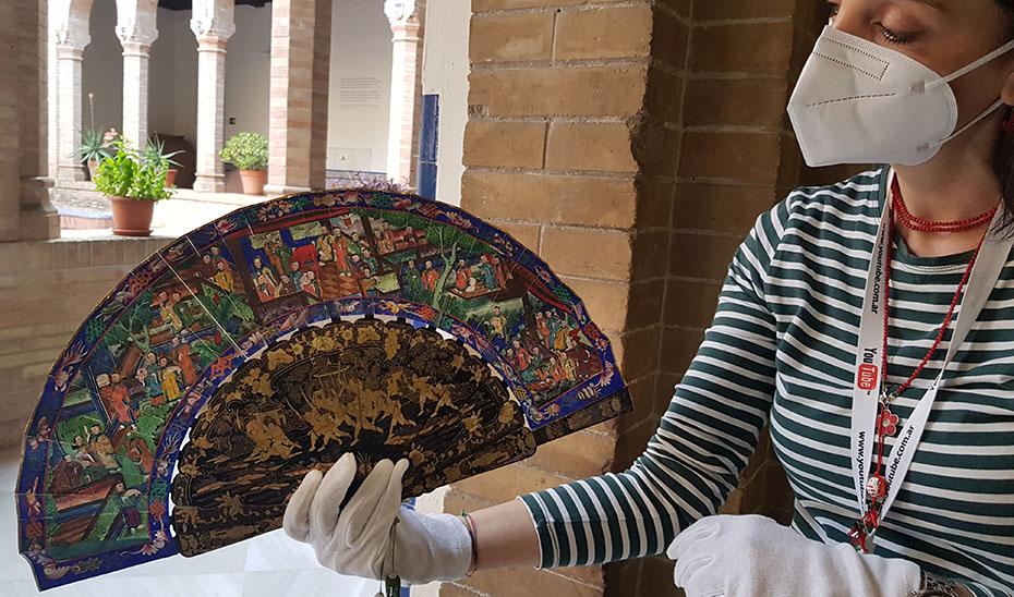 Elena Hernández, conservadora del Museo de Artes y Costumbres Populares de Sevilla, muestras uno de los abanicos de las mil caras expuestos en el recinto.