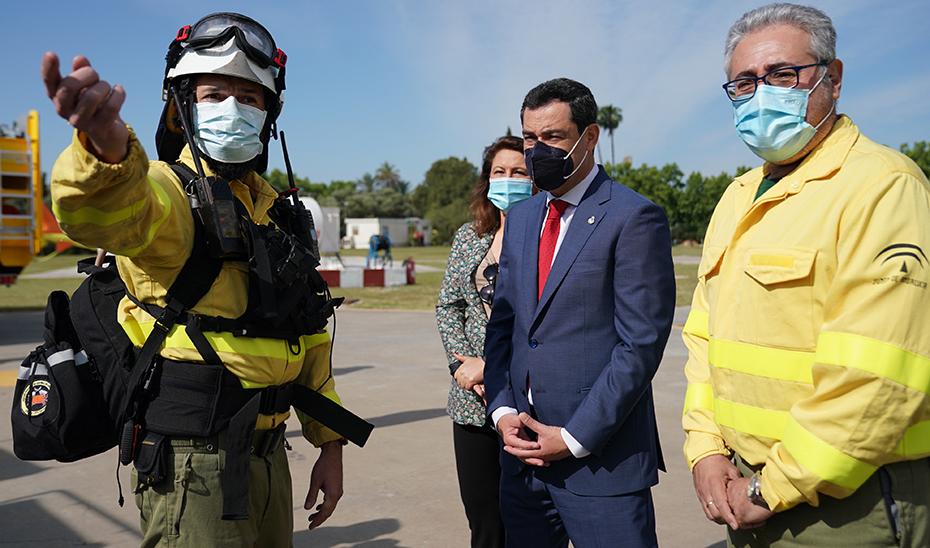 El presidente de la Junta, en el helipuerto de la Cartuja, en Sevilla, con personal del Infoca.