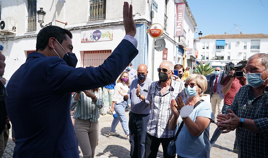 Juanma Moreno saluda a los vecinos de Pilas en su recorrido por el municipio sevillano.