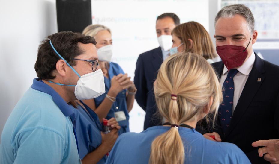 El consejero Elías Bendodo conversa con unos enfermeros en el inicio del proceso de vacunación en la empresa Alestis Aerospace.