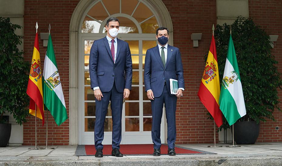 El presidente andaluz, Juanma Moreno, en la escalinata de la Moncloa junto a Sánchez.
